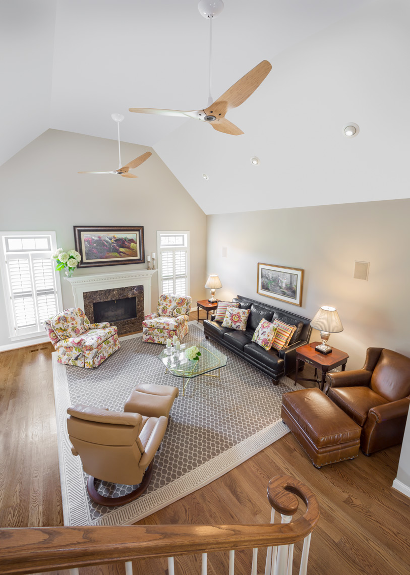 traditional open living room with ceiling fans