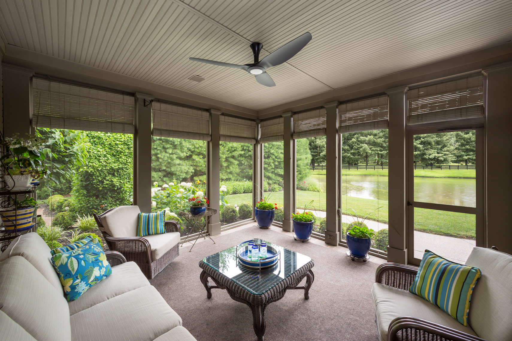 Screened porch with Haiku Fan overlooking lush landscaping and lake