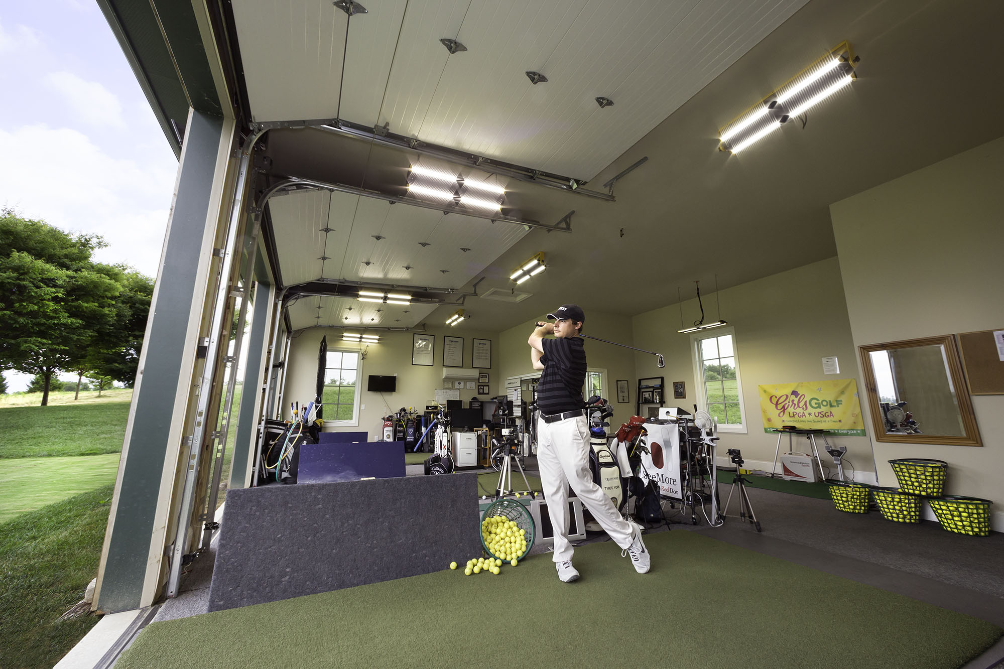 man swinging club in well lighted interior midday at golf training center