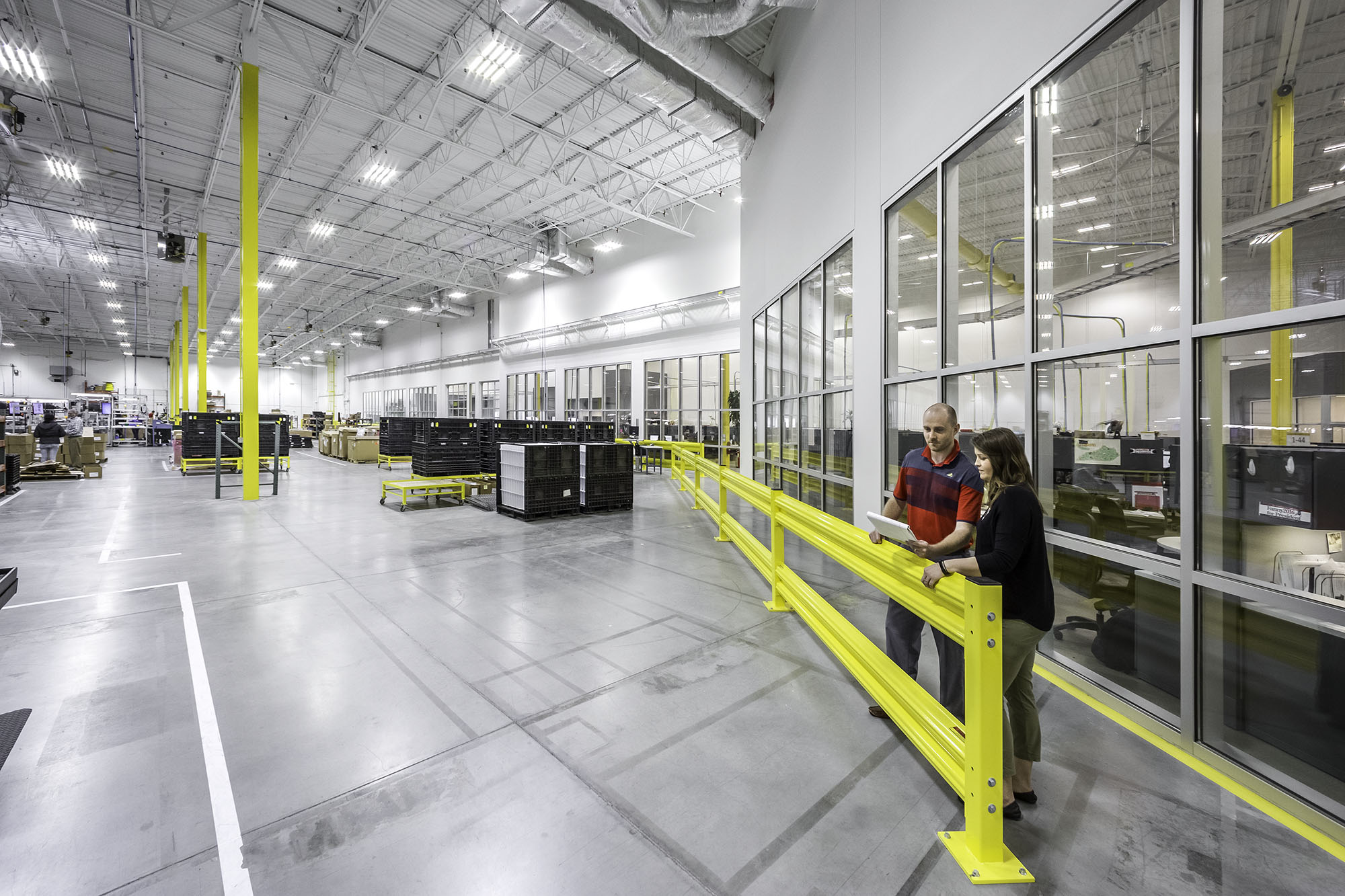 two employees confer in modern well lit manufacturing facility