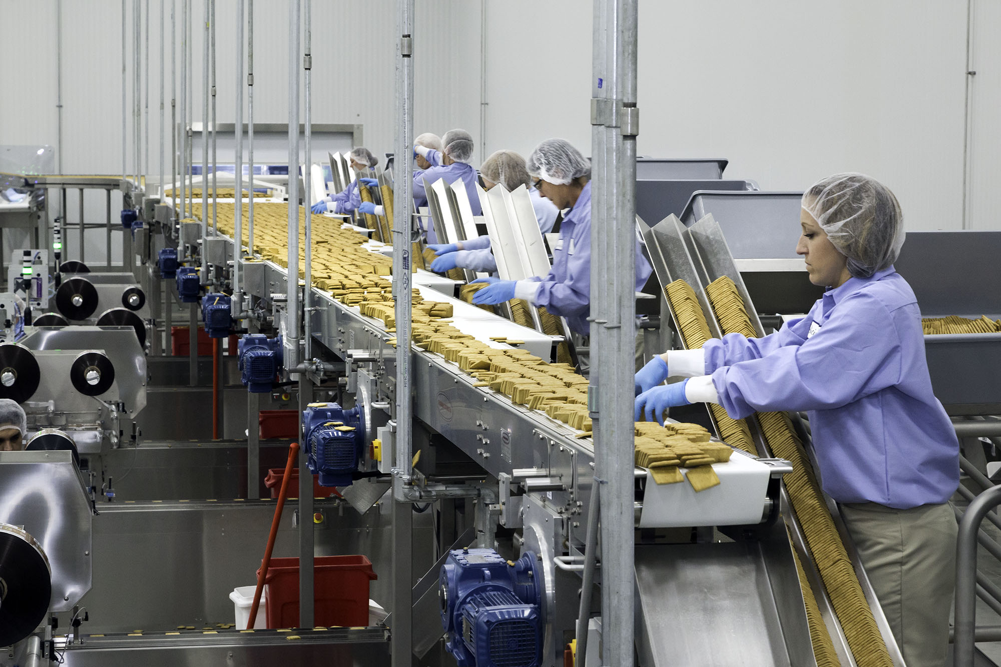 woman tending cracker packaging line at bakery