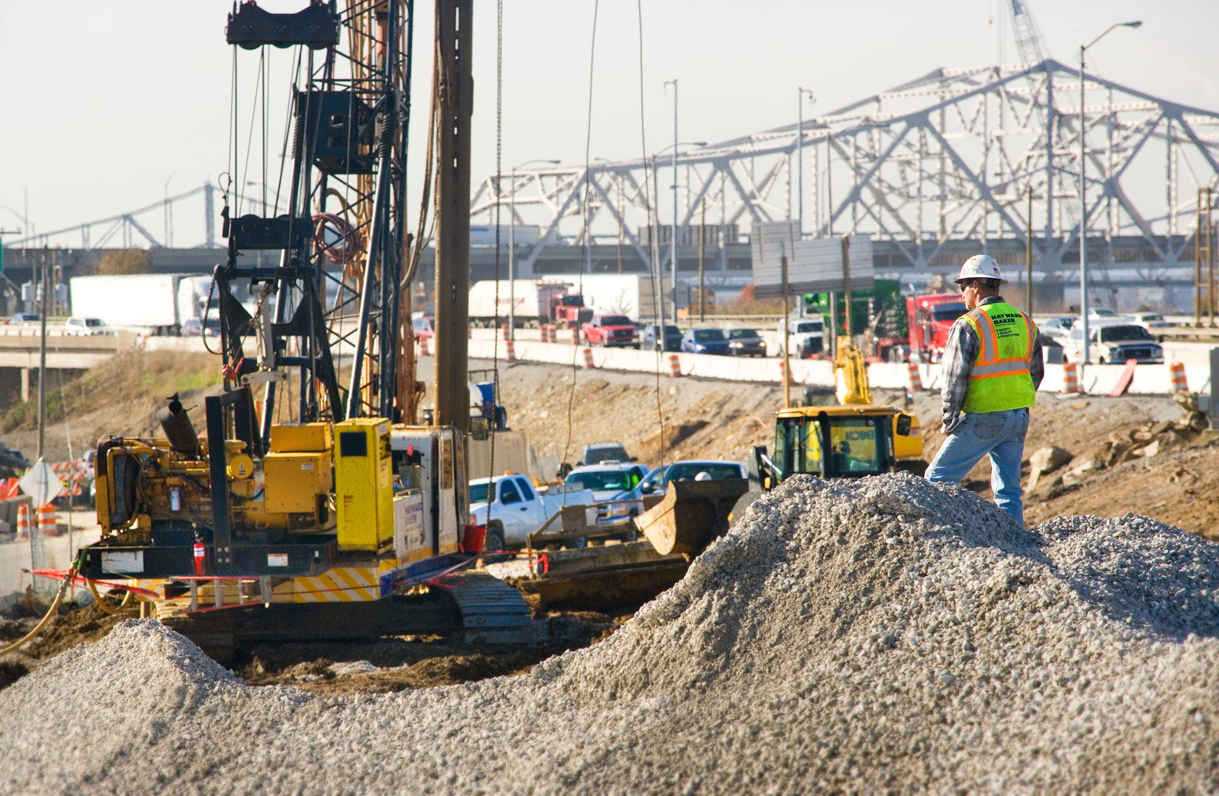 Construction worker supervising pile boring for bridges