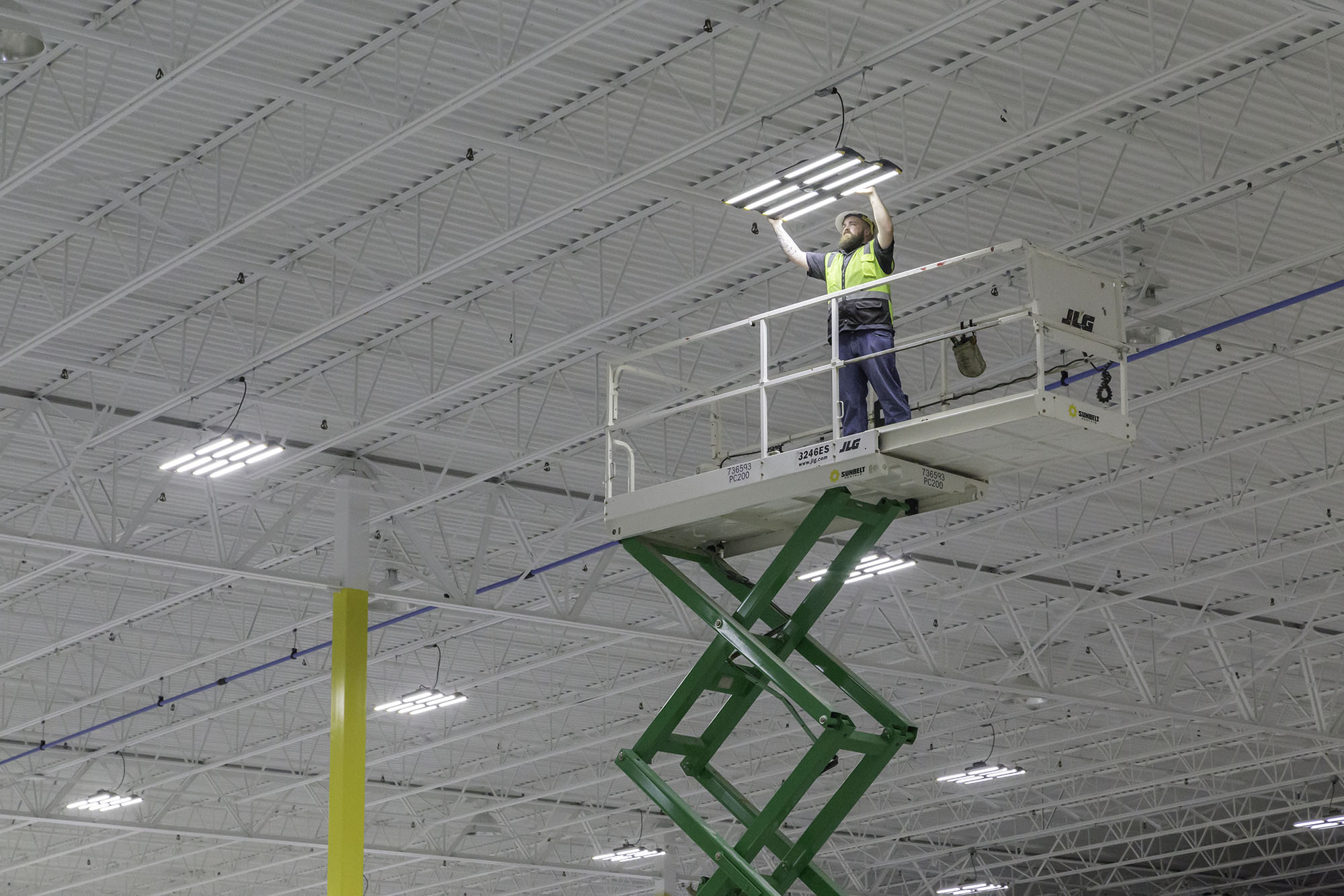 worker on scissors lift installed led lighting in manufacturing facility