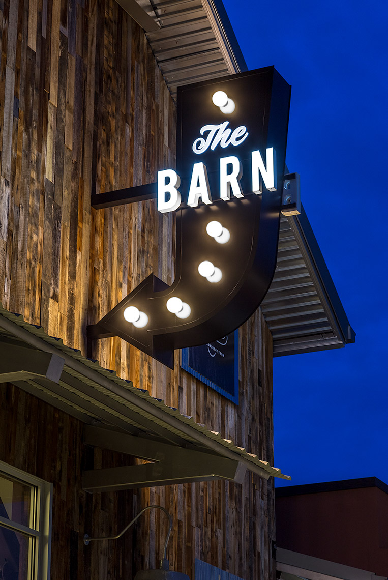 nighttime view of lit blade sign at the summit barn